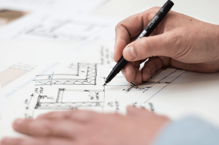 Design - Architect with pen in hand doing house sketches